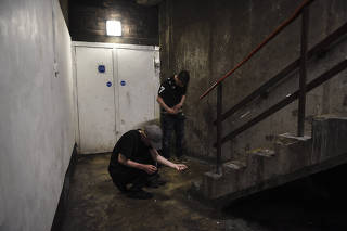 James Muir, left, and Tony Nugent use heroin in a stairwell popular with addicts in Glasgow, Scotland, July 27, 2019. (Mary Turner/The New York Times)