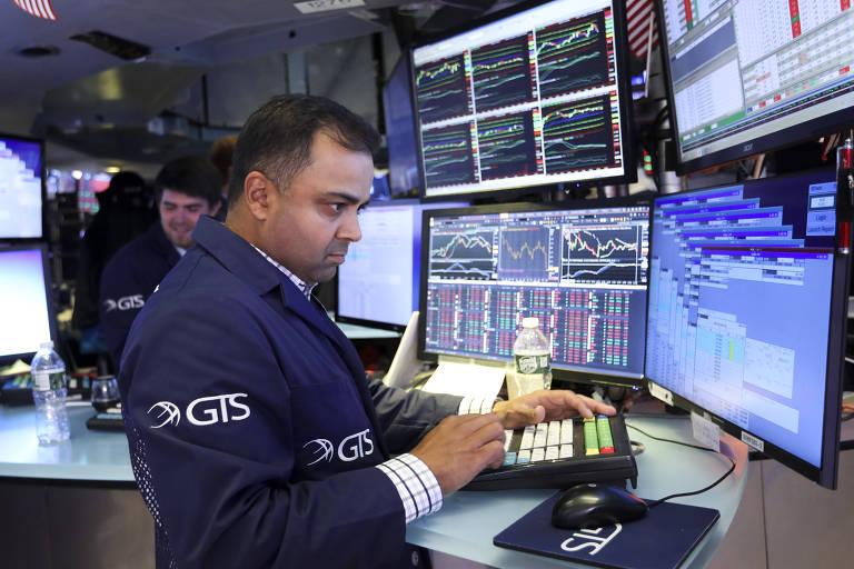 Corretor analisa telas na Bolsa de Nova York