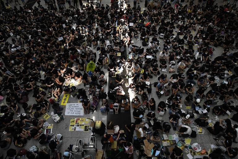 Vestidos de preto e com cartazes, manifestantes fazem ato no aeroporto internacional de Hong Kong