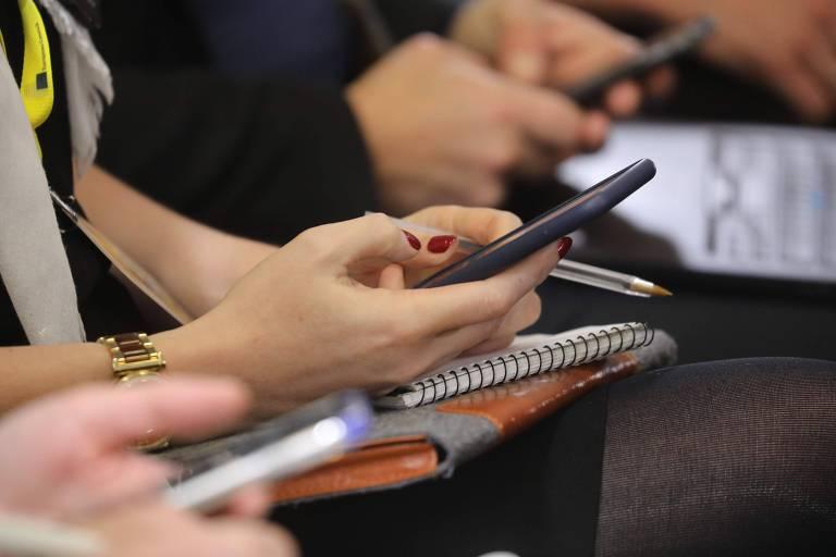 Foto fechada de mãos de três pessoas usando o celular