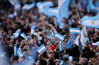 People wave flags as presidential candidate Alberto Fernandez and running mate former President Cristina Fernandez de Kirchner speak during their closing campaign rally ahead of primary elections, in Rosario, Argentina