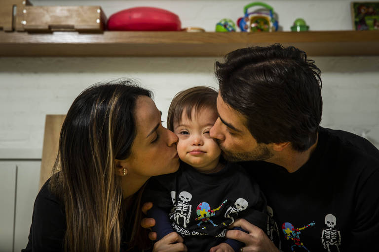 Henri e Marina beijam o filho, Pedro, durante sessão de fisioterapia