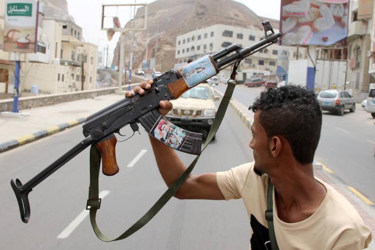 No meio da avenida, integrante das forças separatistas do sul segura arma, AK-47. No cabo da arma,  há uma foto de Muneer al-Yafee, general iraniano morto em um ataque de míssil em 2019, em Aden - Agosto, 2019.