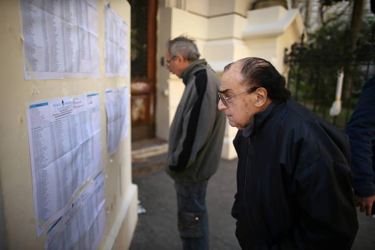 Um homem procura seu nome na lista de votação das primárias argentinas, em Buenos Aires