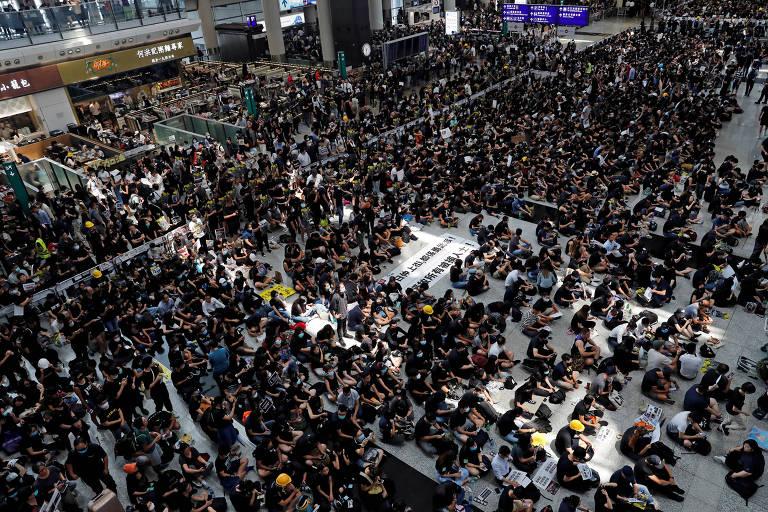 Manifestantes fazem ato no aeroporto internacional de Hong Kong, nesta segunda-feira (12)