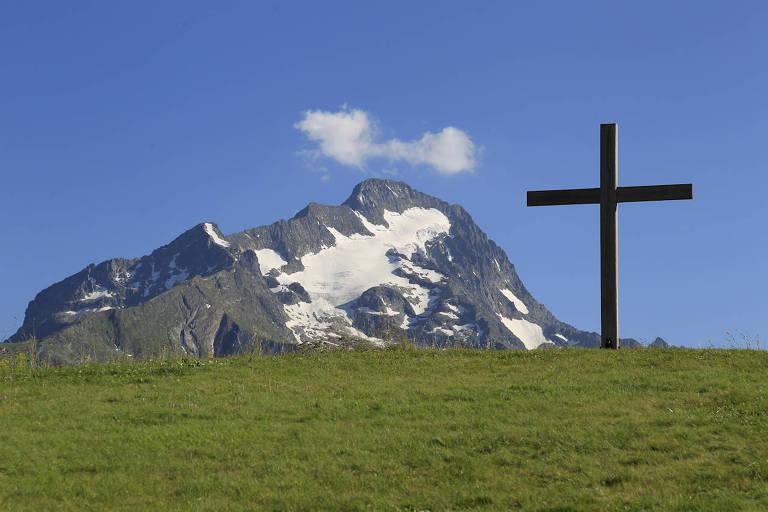 Montanha com um pouco de neve e uma cruz a frente