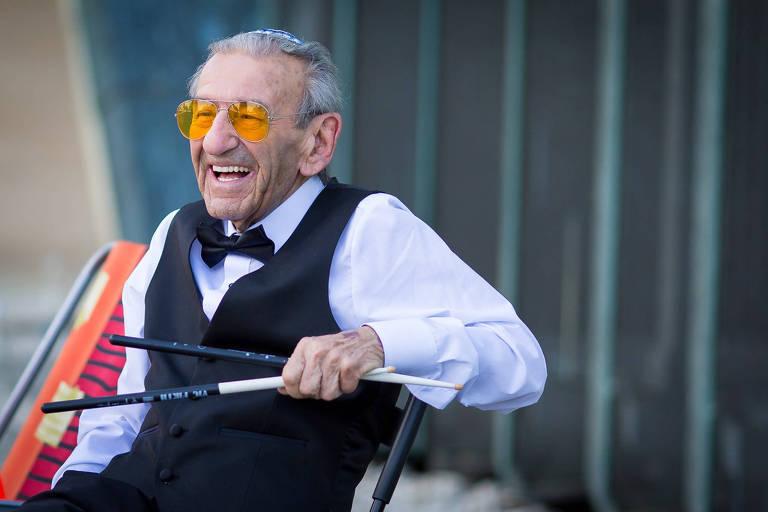 homem velho de óculos laranja tocando bateria