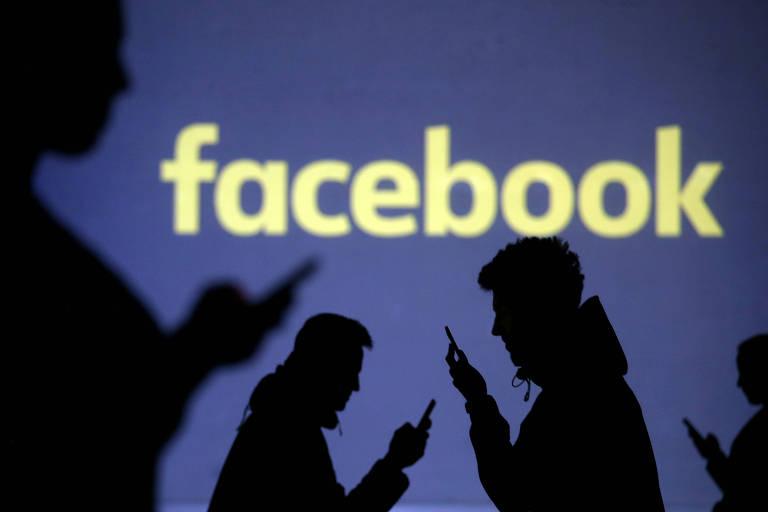 Silhuetas de pessoas mexendo no celular com logo do Facebook ao fundo