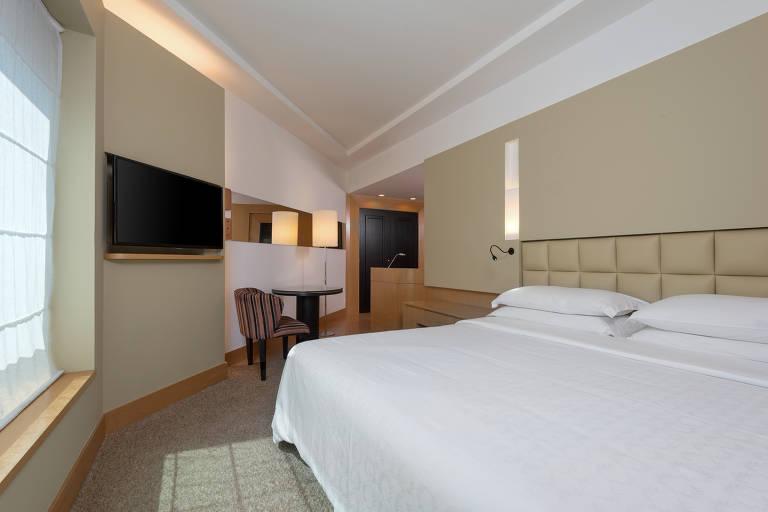 Quarto com cama e televisão na parede
