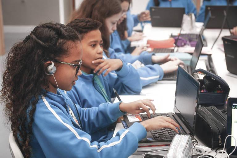 Menino e menina adolescentes estudam juntos em uma mesa na Escola Mais