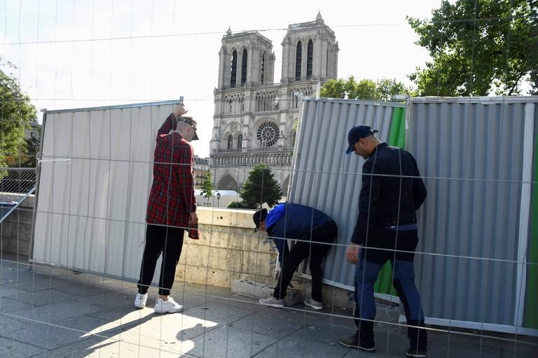 Funcionários instalam tapumes para isolar a área da catedral para descontaminação