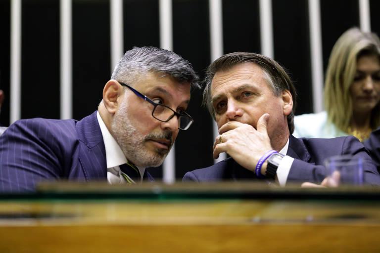 Com mão na boca, o presidente Jair Bolsonaro conversa com Alexandre Frota na Câmara