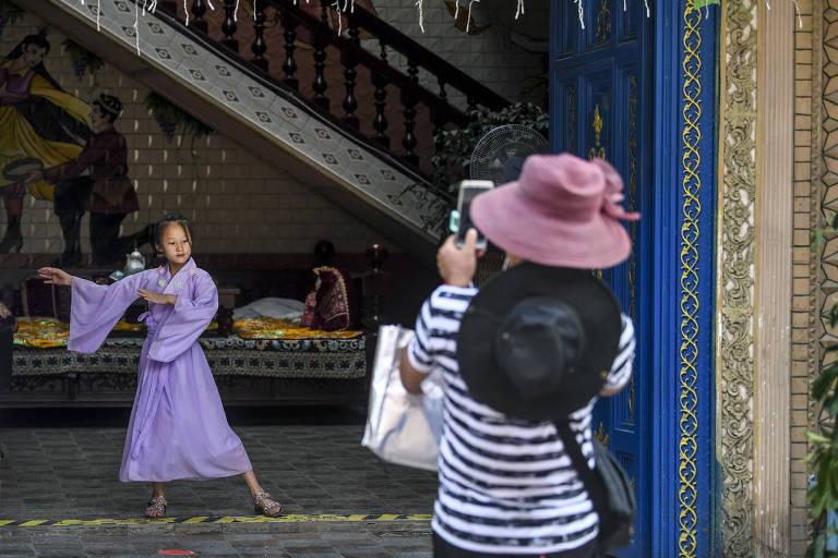 Uma garota posa para fotos na antiga cidade de Kashgar, região autônoma de Xinjiang Uygur, noroeste da China