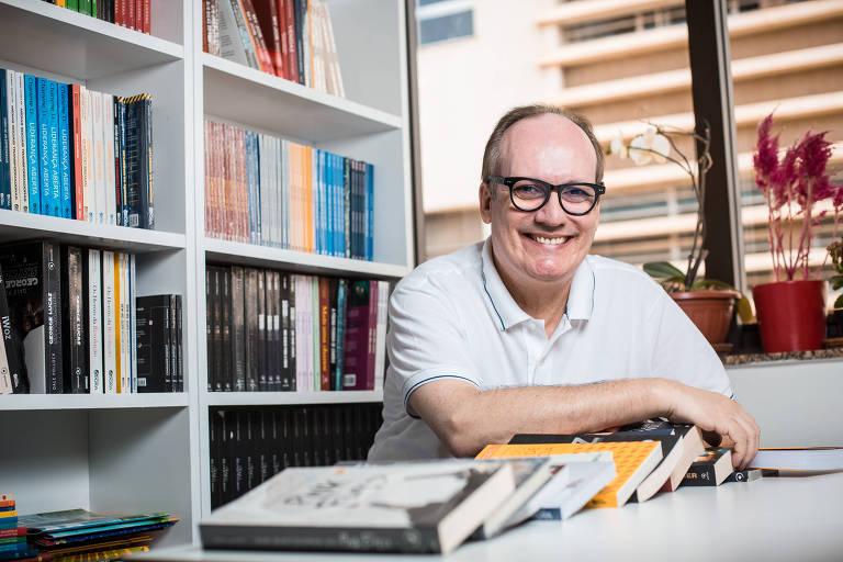 Homem sentado em mesa com livros, sorrindo
