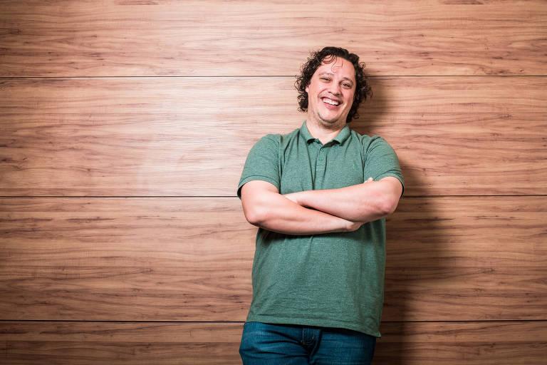 Homem de verde, sorrindo, com parede de madeira atrás