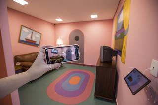 Consumo 4.0. Cliente faz foto de celular para publicar no istagram  de sala decorada baseada nos  Simpsons  da loja Mobly (loja digital que acabou de abrir um espaco fisico tambem).