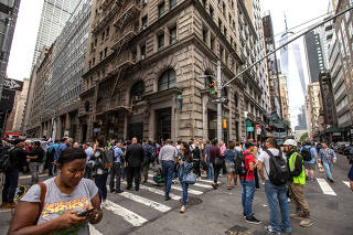 Commuters are seen on Fulton Street after the Fulton Street subway station was closed as police investigated two suspicious packages in Manhattan