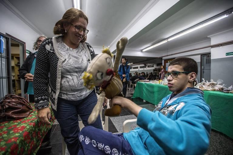 Maria Alcinda Castor de Melo, 48, observa o filho Gabriel, 22, autista, com um velho palhacinho de pano na mão
