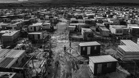 CIDADE DO CABO, ÁFRICA DO SUL, 03.07.2019 - Mulher carrega balde de água na cabeça em uma rua de terra em Khayelitsha, a maior township (favela), na Cidade do Cabo, e uma das maiores da África do Sul. (Foto: Lalo de Almeida/Folhapress)