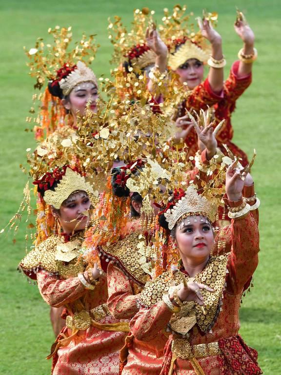 Grupo de mulheres em vestes tradicionais dança