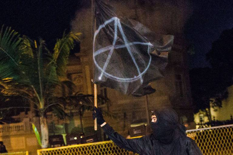 homem com bandeira da anarquia