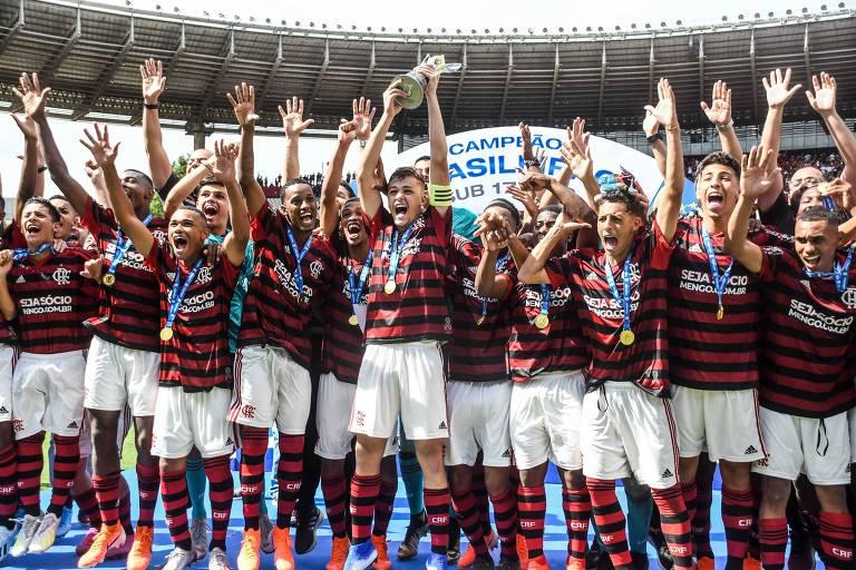 Os adolescentes jogadores do Flamengo estão enfileirados, no pódio e juntos erguem a taça do campeonato. Os jovens sorriem e tem feições alegres.