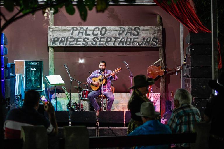 Homem com violão em palco se apresenta para plateia vazia. Atrás dele, uma placa diz Palco das Raízes Sertanejas