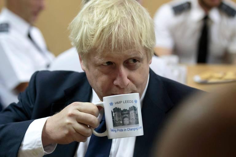 O primeiro-ministro britânico, Boris Johnson, bebe em uma caneca enquanto conversa com funcionários de prisão em Leeds