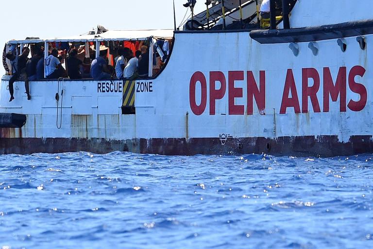 """Pessoas se concentram na área externa do barco, que parece lotado. O barco é branco e seu nome, """"Open Arms"""", está escrito na lateral com letras vermelhas"""