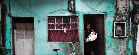 Mulher segura sua filha no colo em frente à sua casa, na Barrinha, comunidade que fica na Zona Oeste do Rio e que está sendo ameacada de despejo. Ian Cheibub/Folhapress