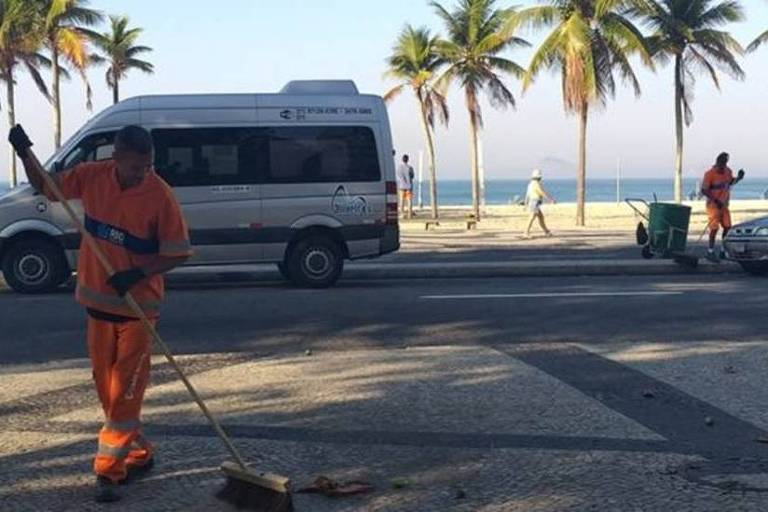Os garis Alexander Santos Pereira e Sérgio Jesus Teixeira são parte da equipe que faz a limpeza do Leme, no Rio