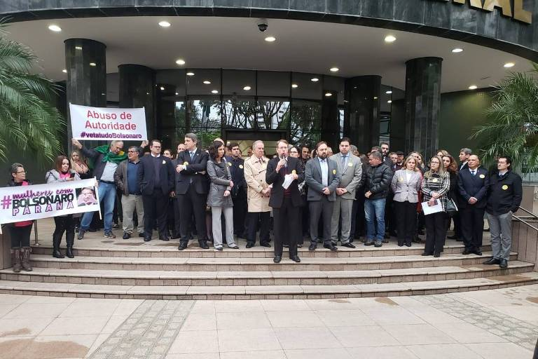 Organizadores do ato pediram que mulheres retirassem faixa, à esquerda, em evento com procurador Deltan Dallagnol (no canto direito)