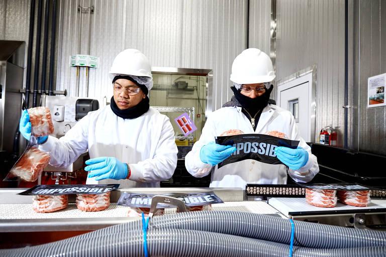 Operários manipulam embalagens com hambúrgueres vermelhos, sobre esteira com diversas outras embalagens