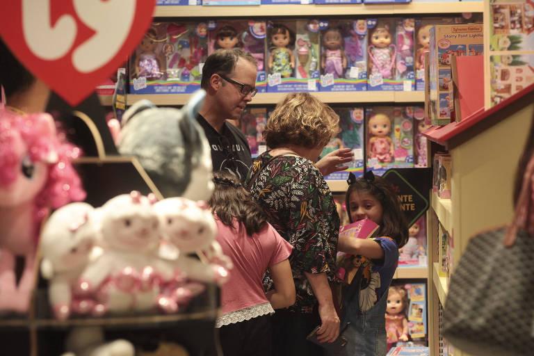 Casal e filha escolhem brinquedos na seção de bonecas