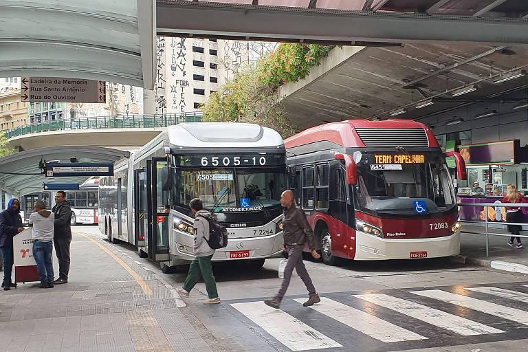 Dois ônibus, um cinza e outro vermelho, em terminal; pessoas atravessam faixa de pedestres