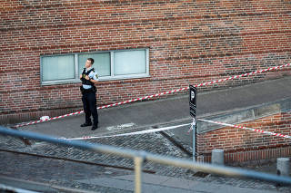 A police officer stands in front of the Danish Tax Authority office building at Oesterbro, where an explosion occured near Nordhavn Station, in Copenhagen