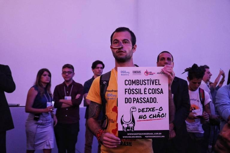 """Ministro do Meio Ambiente, Ricardo Salles, discursou sob protesto da ONG 350. """"Enquanto os incêndios se acirram na Amazônia, o Ministro do Meio Ambiente do Brasil atende a #ClimateWeekLACC em Salvador para fingir que há um futuro nos combustíveis fósseis. Ativistas estavam lá para chamar seu blefe"""", diz publicação da organização"""