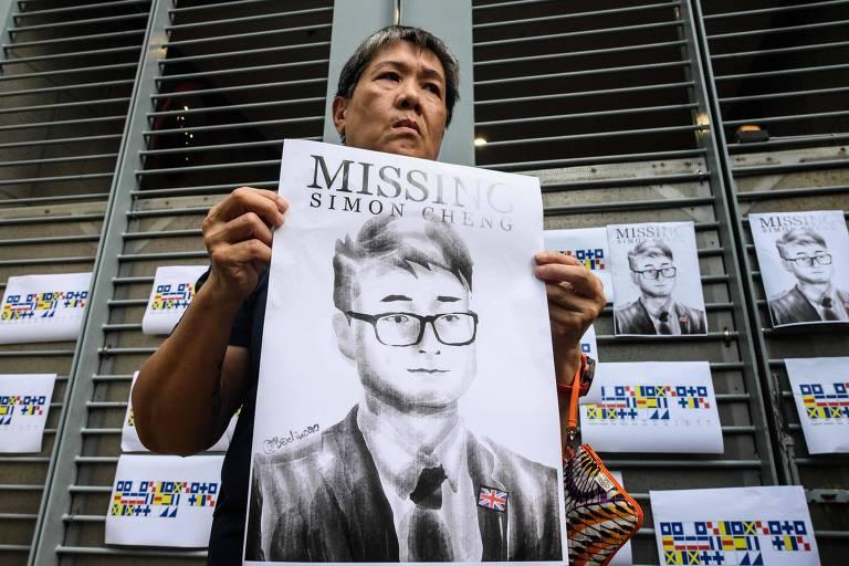 Manifestante segura cartaz com ilustração do rosto de Simon Cheng durante protesto contra sua detenção em frente ao consulado britânico em Hong Kong