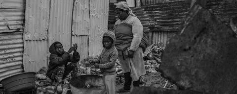 Cidade do Cabo, África do Sul. 03/07/2019. DESIGUALDADE GLOBAL. Família se esquenta em uma fogueira improvisada em Khayelitsha, a maior township ( favela ) da Cidade do Cabo, e uma das maiores da África do Sul. As casas são construídas de telhas metálicas e não são suficientes se proteger do frio do inverno. ( Foto: Lalo de Almeida/ Folhapress )***EXCLUSIVO FOLHA***