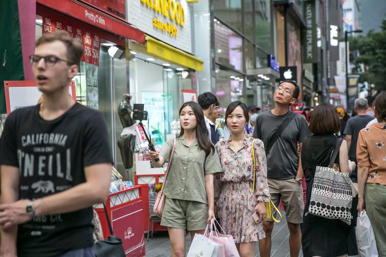Kang Na-ra, à esquerda, filma a si mesma enquanto caminha pelas ruas de um distrito comercial em Seul, Coreia do Sul (Jean Chung/The Washington Post)