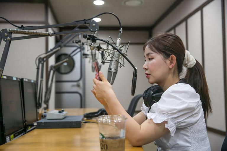 Han Song-ee checa seu celular antes do programa de rádio que apresenta em Seul começar (Jean Chung/The Washington Post)