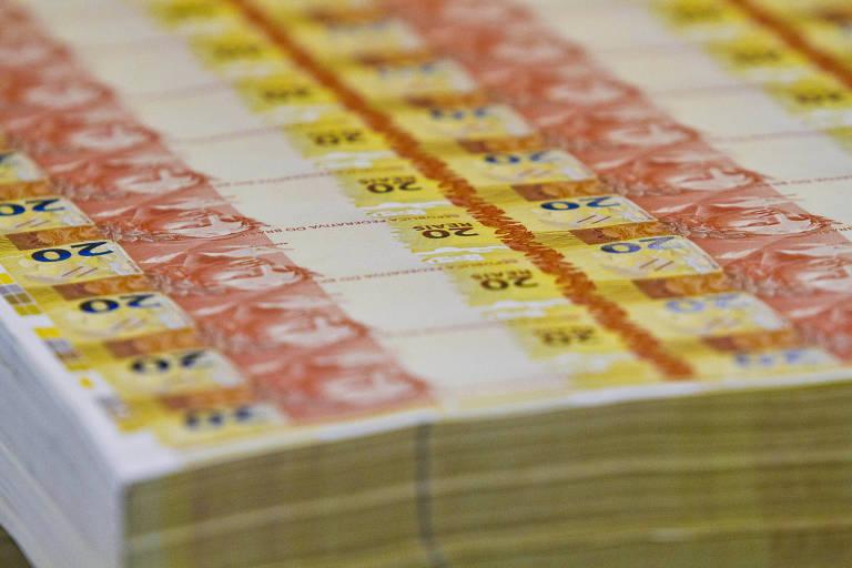 Na foto, várias cédulas de uma nota de R$ 20 aparecem empilhadas em uma área da Casa da Moeda