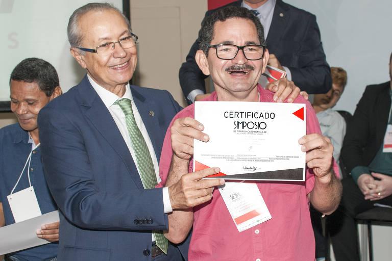 Francisco Sebastião de Lima, sorridente, segura certificado