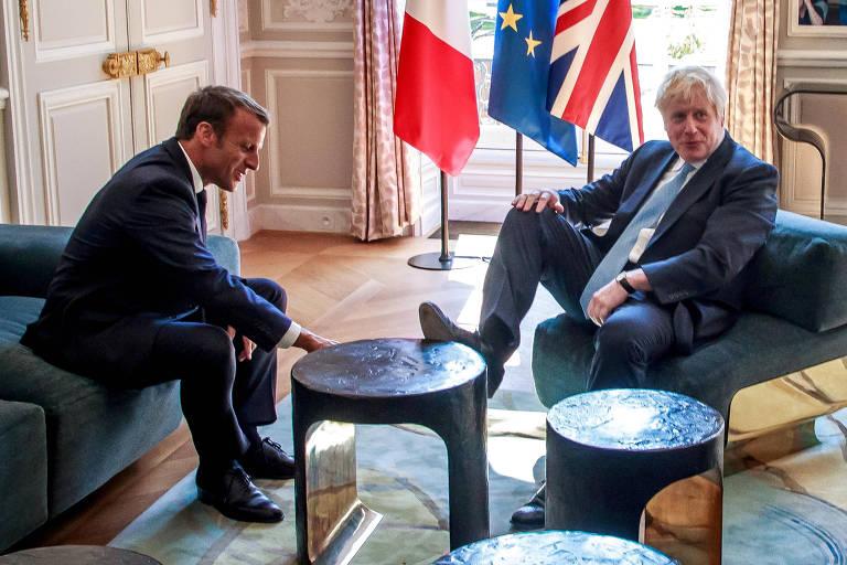 O premiê britânico, Boris Johnson, coloca os pés em mesa de centro durante encontro com Emmanuel Macron no palácio do Elysée