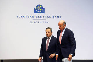 European Central Bank President Draghi and Vice-President de Guindos leave a news conference at the ECB headquarters in Frankfurt