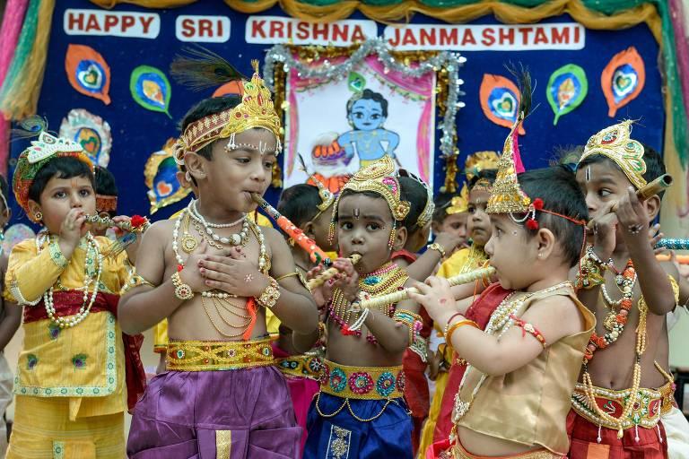 Crianças vestidas como deus hindu Krishna, com roupas colorias e adereços, tocam flautas