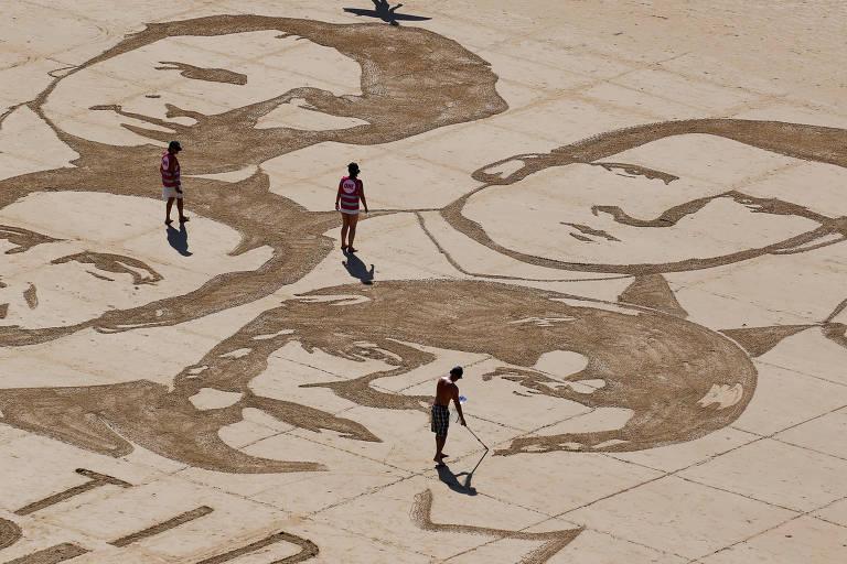 Rostos dos líderes do G7 reproduzidos em areia pelo artista Sam Dougados em Biarritz, sul da França