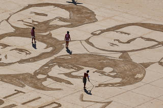 Local Basque sand artist Sam Dougados reproduces the faces of the G7 leaders in the sand on a beach in Biarritz on the eve of the Biarritz G7 summit