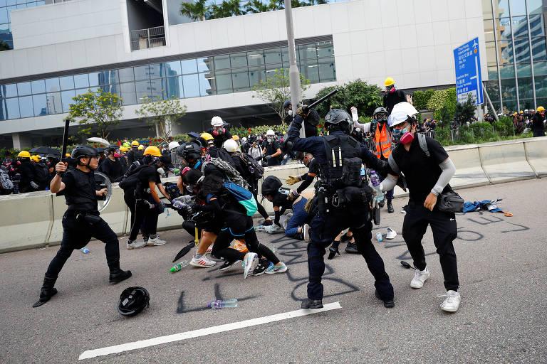 Manifestantes caídos no chão apanham de guardas com cassetetes