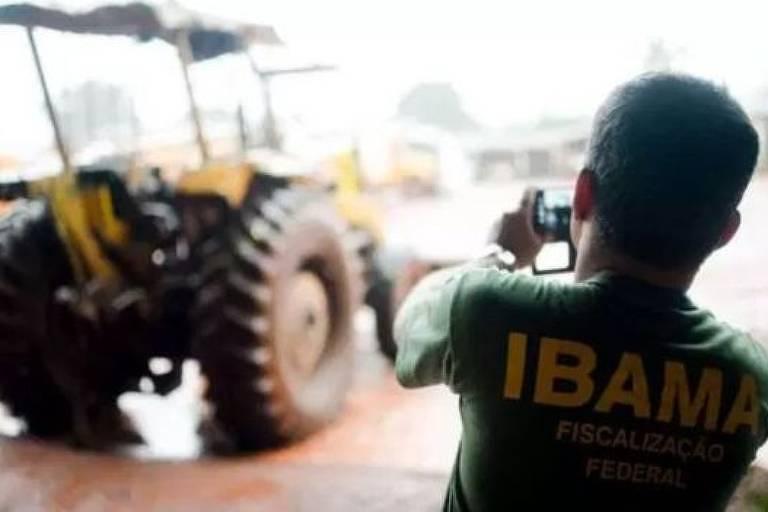 Fiscal do Ibama fotografa trator incendiado.